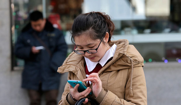 Chinese people check on their smartphones on a street in Beijing on February 16, 2015.