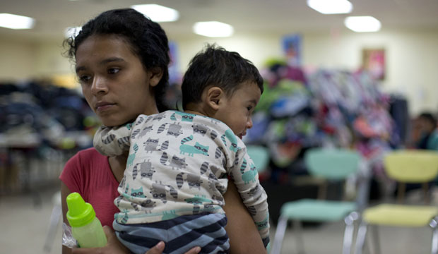 A mother holds her 14-month-old son at Sacred Heart Catholic Church in McAllen, Texas.