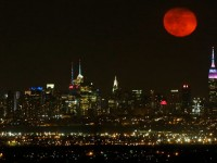 The moon rises over New York City