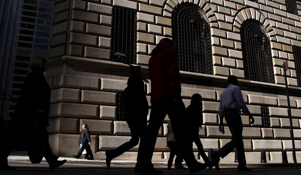 Pedestrians walk past the Federal Reserve Bank of New York in October 2012.