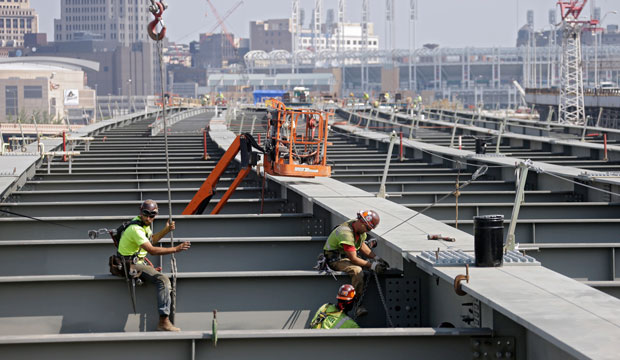 Ironworkers secure a cross member on a highway bridge under construction in Cleveland, August 2013.