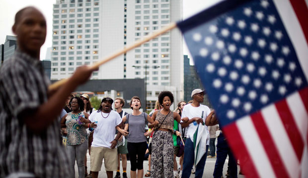Protesters link arms as they block an intersection in the Buckhead neighborhood of Atlanta during a march against the recent police shootings of African Americans on Monday, July 11, 2016.