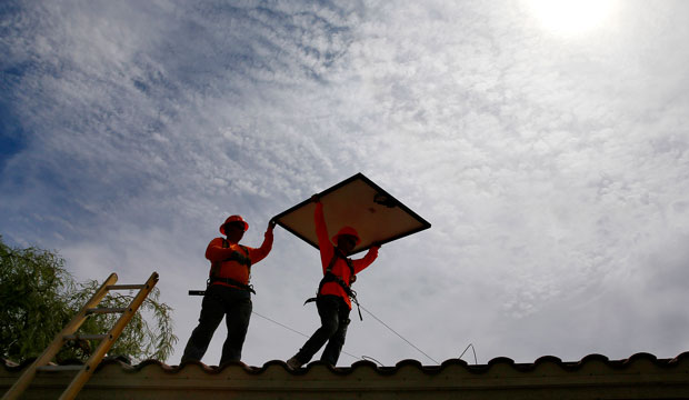 Electricians install solar panels on a roof in Goodyear, Arizona, on July 28, 2015.