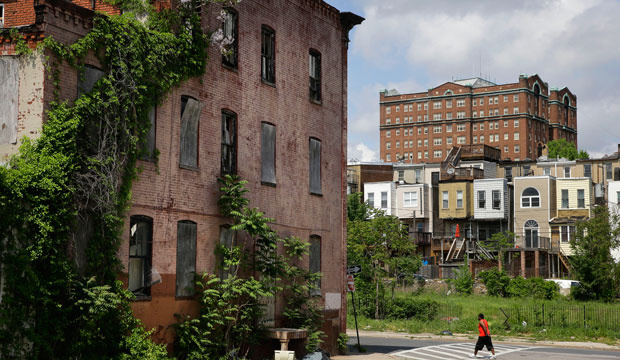 A man walks past a blighted building in the Penn-North neighborhood of Baltimore, with a residential tower in the Reservoir Hill neighborhood in the background at top right, on May 9, 2015.