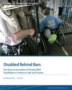 A prisoner in a wheelchair goes through a door