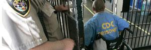 A prisoner in a wheelchair goes through a door