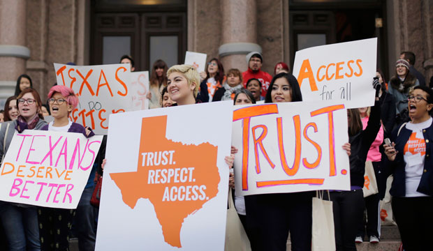 College students and abortion rights activists hold signs during a rally on the steps of the Texas Capitol, in Austin, Texas, on February 26, 2015.