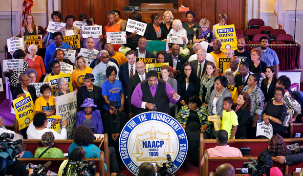 North Carolina NAACP president Rev. William Barber, center at podium, speaks at a news conference in Richmond, Virginia, Tuesday, June 21, 2016.