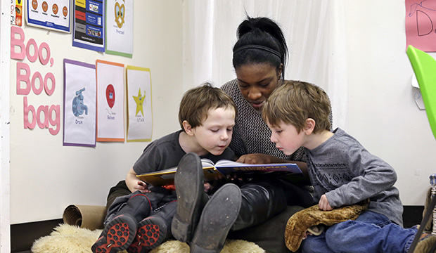 An assistant teacher reads to students at a pre-K school in Seattle, February 12, 2016.