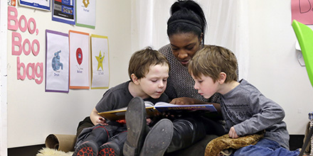 An assistant teacher reads to students.