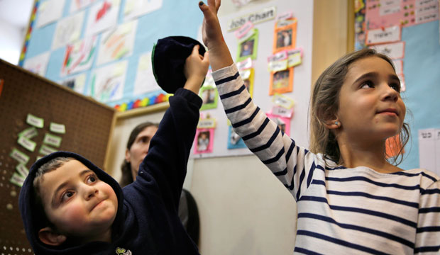 Two children raise their hands in class, March 2015.