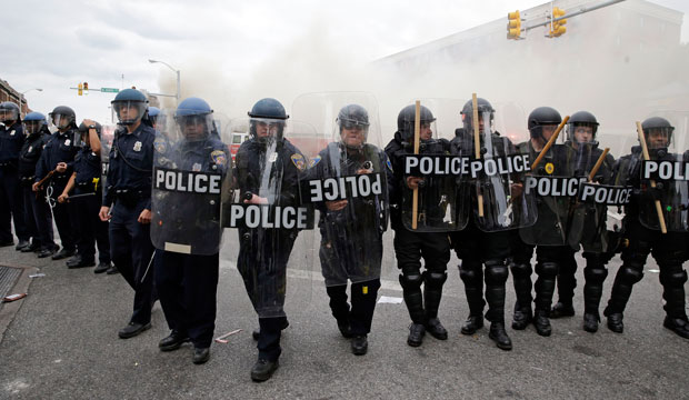 Police advance toward protestors as a store burns following the funeral of Freddie Gray on April 27, 2015, in Baltimore.