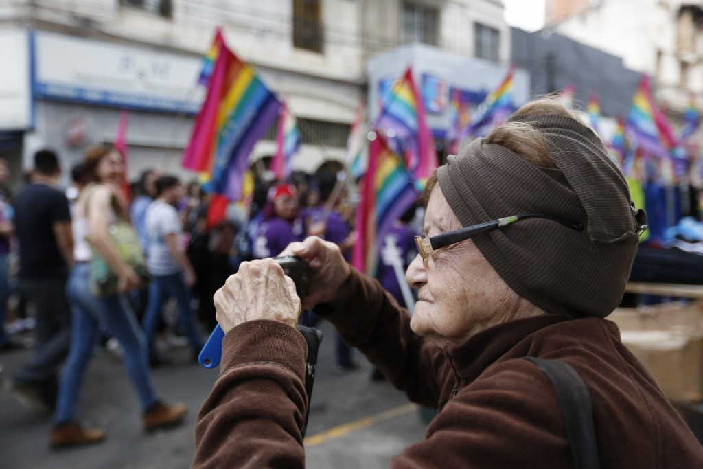 An elderly woman takes pictures of a gay pride parade on July 9, 2016.