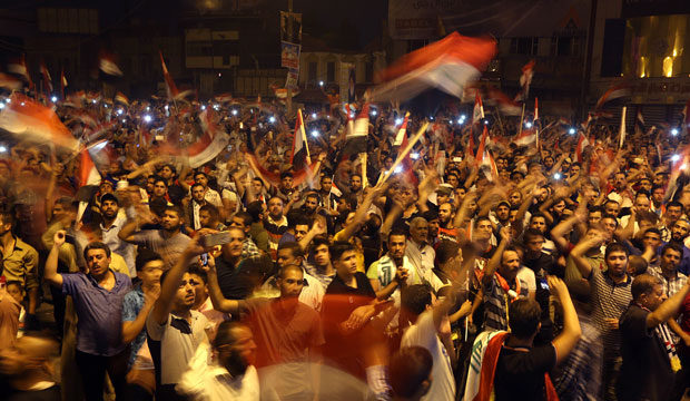 Protesters wave national flags during a demonstration in Tahrir Square in Baghdad, Iraq, on October 2, 2015.