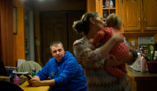 A man sits at the kitchen table as his wife holds their daughter in Harlan, Kentucky, on October 18, 2014.