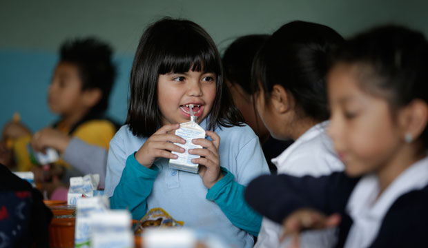 An elementary student drinks her milk in the cafeteria on January 13, 2015, in Los Angeles.