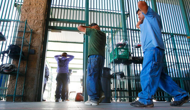Suspected unauthorized immigrants are transferred out of a holding area at the U.S. Customs and Border Protection headquarters in Tucson, Arizona, on August 9, 2012.