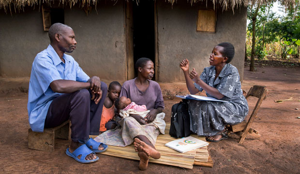 A community health worker visits with a family on July 21, 2014, in Mbale, Uganda.