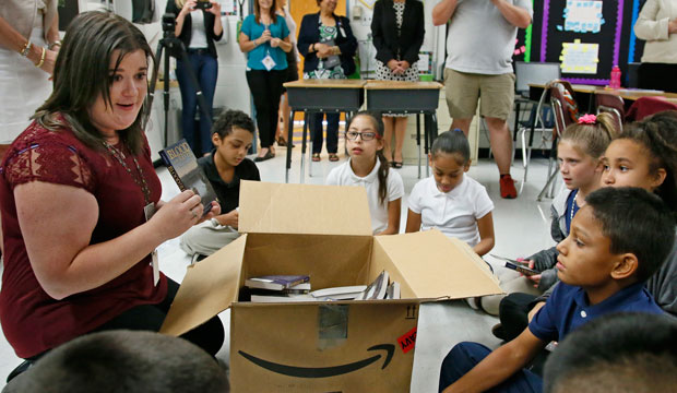 An Oklahoma City fifth-grade teacher passes out books to her class on August 3, 2016.