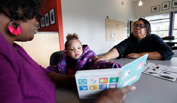 Taliyah Garrett reads as her mother, Tawana Brooks, follows along with coordinator Jazmyn Scott after Taliyah during a Parent Child Home Program visit in Seattle, December 2011.