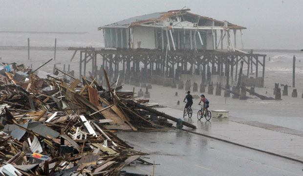 Cyclists ride past debris piled along on the seawall road in Galveston on September 14, 2008, after Hurricane Ike hit the Texas coast.