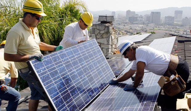 Workers install solar electrical panels on the roof of a home in Glendale, California, on March 23, 2010.
