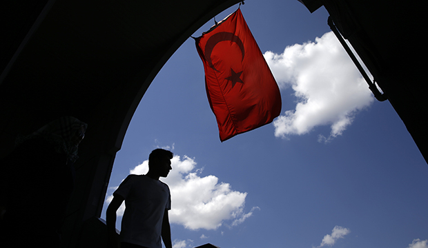 A pedestrian passes under a Turkish flag in Istanbul, August 14, 2016.