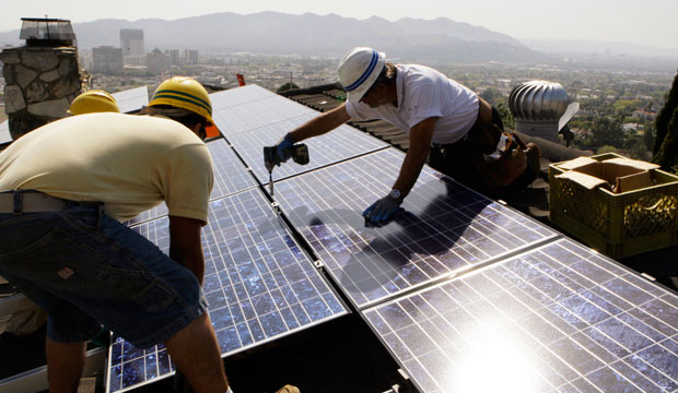 Installers install solar electrical panels on the roof of a home in Glendale, California, March 2010.