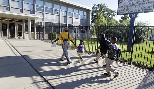 Parents drop their children off at school.