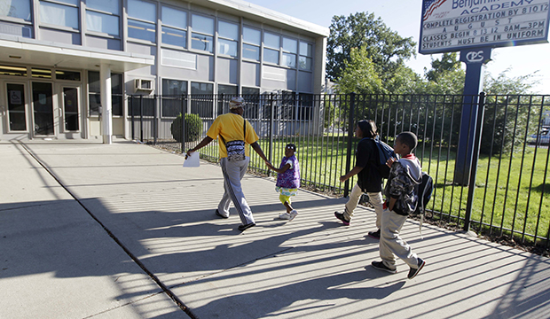 Parents drop their children off at Chicago's Benjamin E. Mays Academy, September 2012.