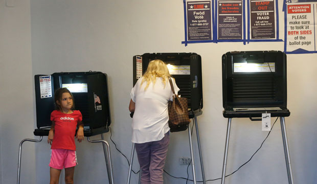 A young girl waits as a voter casts her ballot in the Republican and Democratic primaries at a polling station at the Miami Beach City Hall, March 2016.